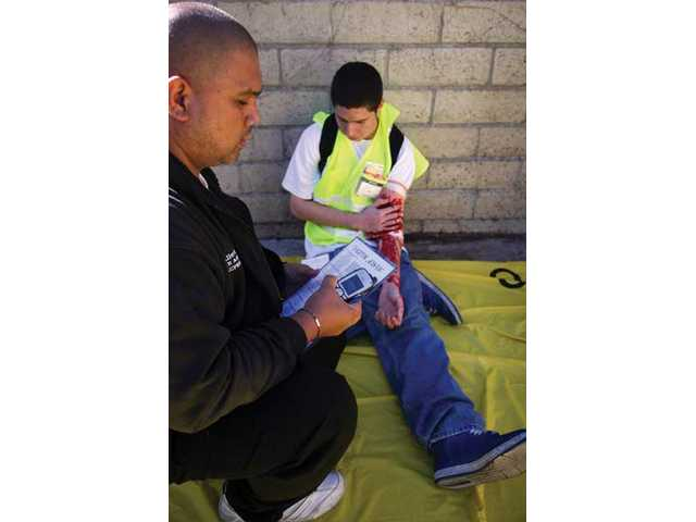 Allen Cumigad, E.R. registration supervisor takes notes on victim Michael Osuna during the Great Shake Out exercise at Henry Mayo Memorial Hospital Thursday morning.