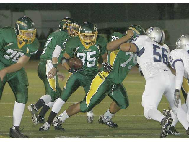 Canyon running back Trent Hernandez (35) rushes against Saugus as teammate Dylan Kawaa (75) blocks Centurion Austin Gonzalez (56) Friday at Canyon High. Hernandez finished with 104 yards and one touchdown in Canyon's 17-10 win.