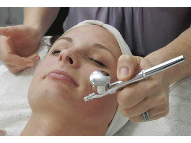 A client at Lavish Salon in Stevenson Ranch receives the ultra-hydrating oxygen facial, which begins with a spray of olive-based oil, from Angela Lark Landy.