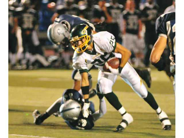 Canyon High's Chris Rivas (25) is brought down by Saugus Centurion Manny Padron (13) Friday in second-quarter action.