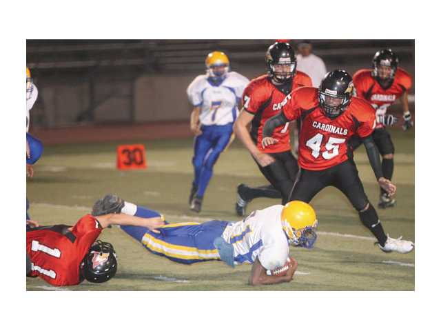 Above, Santa Clarita Christian's Ethan Espinosa makes a tackle as Daniel Chaplin (45) looks on.