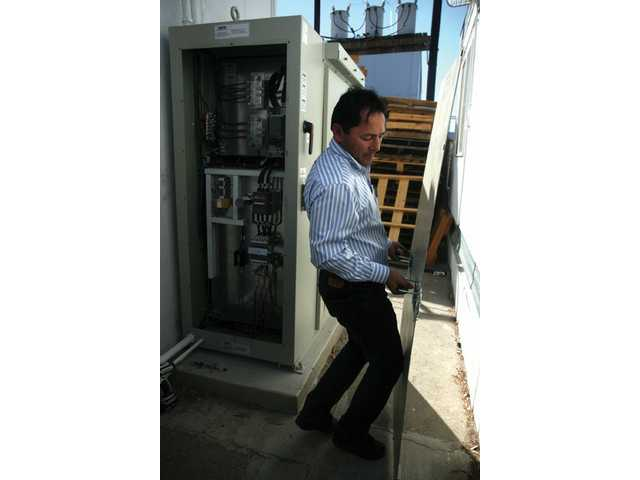 Carlos Vega, field manager from Advance Solar Electric company in Thousand Oaks, checks the solar panel inverter, in which the energy is transferred to outside a building in the Saugus Industrial Center.