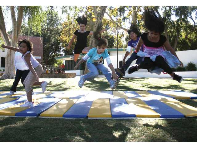 A group of girls from the Boys and Girls Club in Newhall practice cheer stunts Tuesday afternoon outside the clubhouse. Two former Hart High School cheerleaders volunteer two days a week and teach girls cheer routines.