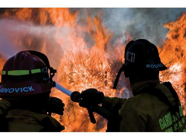 A firefighter from San Gorgonio battles the Sayre Fire as it enters the Newhall Pass Saturday.