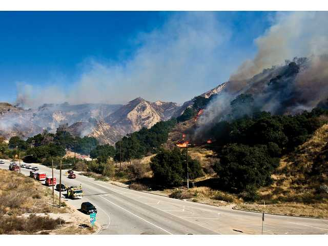 Firefighters in the Newhall Pass light a backfire to help stop the Sayre Fire as it enters the Santa Clarita Valley Saturday.