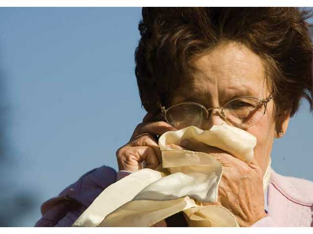 Oralia Leigsring covers her mouth as she makes a phone call to tell someone her mobile home was burned Saturday.