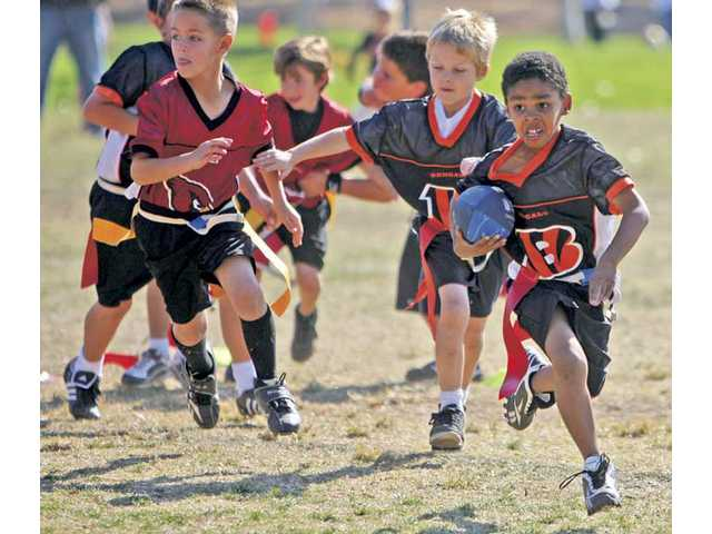 Eight-year-old Julian Robotham runs the ball for his Bengals team during their Super Bowl game against the Cardinals at Central Park in Saugus on Saturday.