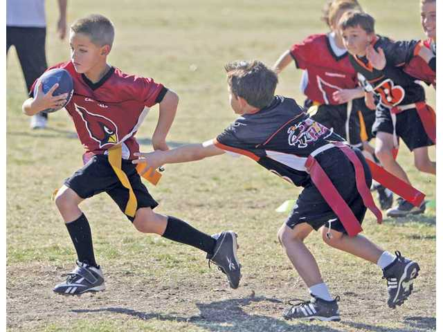 Eight-year-old Ty Pentberthy of the Cardinals scores the team's first touchdown against the Bengals.