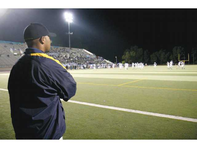 College of the Canyons cornerbacks coach Sirr Guy Shakir watches a football game between Valencia High and Saugus High on Nov. 6 at Cougar Stadium. The COC staff puts in long hours and travels all over Southern California to scout talent.