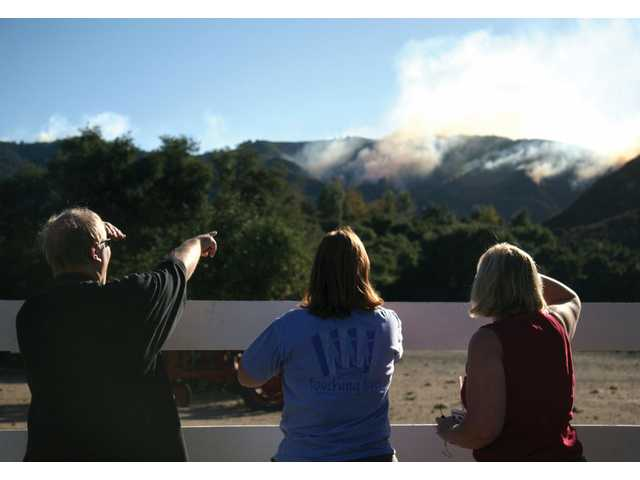 Chip Meyer, left, Sharon Meyer and Charlotte Miller watch as the Sayre Fire burns through the south ridge of Placerita Canyon Road Saturday afternoon.