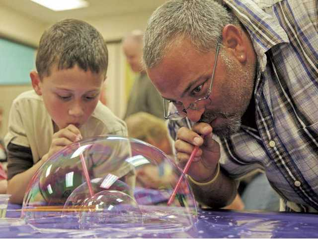 Steve Lasdon and 8-year-old son Tyler Lasdon, of Saugus, participate in a lung capacity experiment during the sixth annual Science Night at Legacy Christian Academy on Oct 28.
