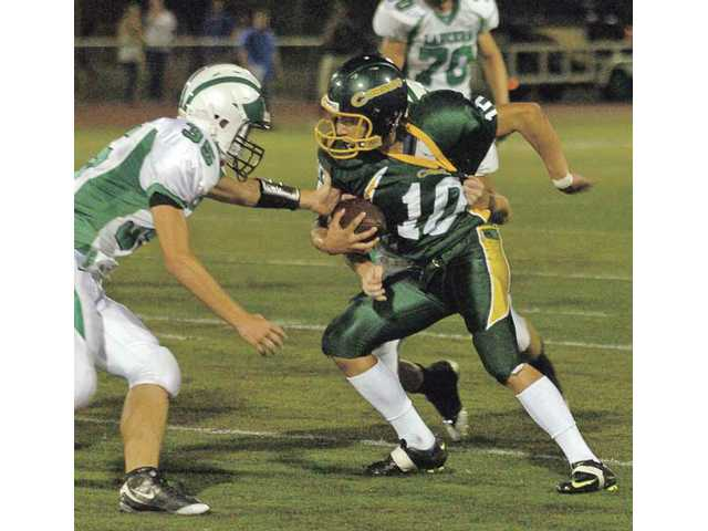 Canyon High wide receiver Shane Habberstad (10) tries to evade Thousand Oaks defenders on Sept. 25 at Canyon. Thousand Oaks will face Valencia in the first round of the CIF-SS Northern Division playoffs on Friday, while the Cowboys will travel to face Moorpark.