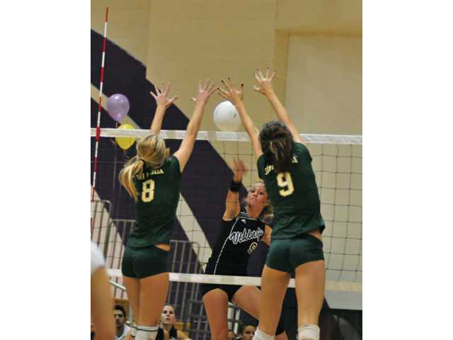 Santa Barbara outside hitter Emily Rottman (8) and mid blocker Hadley Simons (9) attempt to block a returned save by Valencia Vikings  Sydney Striff in the second game at Valencia on Monday night.