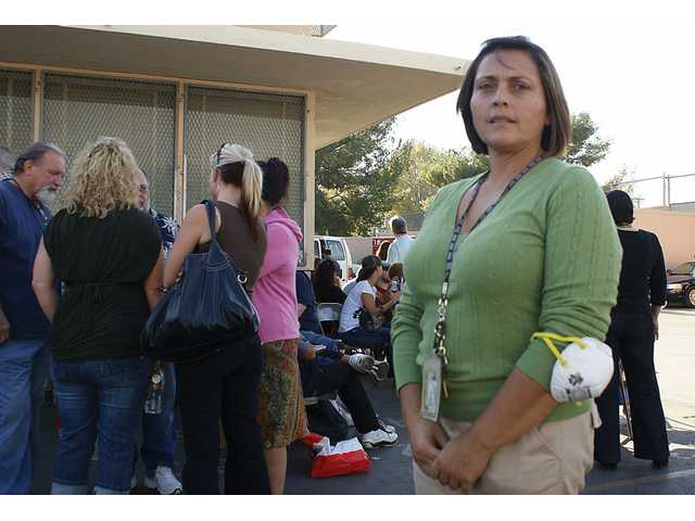 Patricia Attalla stands near a line of Oak Ridge residents waiting to board a bus to the burned out area.