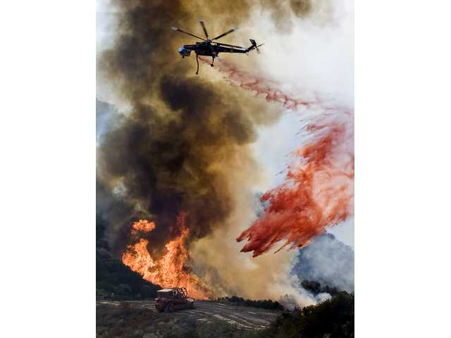 An Erikson Sky Crane helicopter drops fire retardant on the Sayre Fire line in Placerita Canyon as crews fight to keep the fire under control.