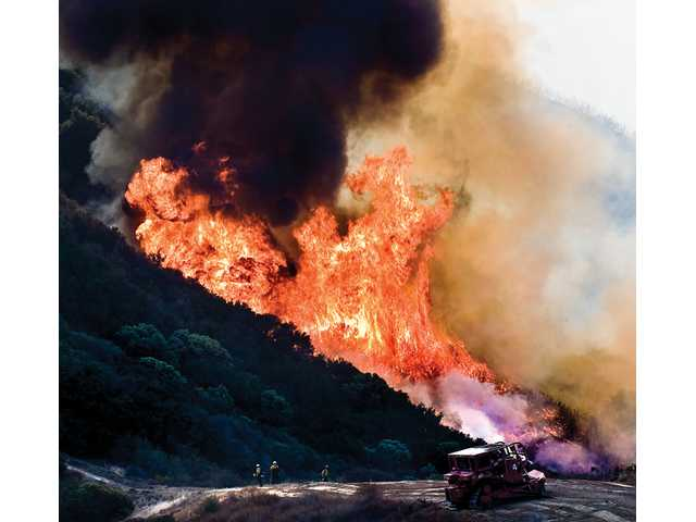 "The Los Angeles County Fire Department's ""Dozer Team 4"" and a U.S. Forest Service Hotshot crew battle the Sayre Fire in Placerita Canyon."