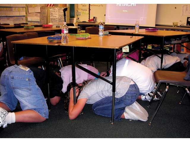 Old Orchard Elementary School students duck and cover under tables in a classroom during the Great Shakeout disaster drill.