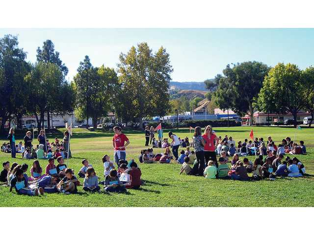 Old Orchard Elementary School students gather on the athletic field during drill. The kids were grouped by class and wore locator cards around their necks.