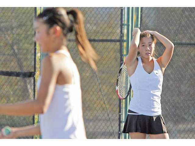 Valencia tennis player Kirstie Kwock, right, reacts to a missed ball during a set Tuesday at Valencia High during the CIF-Southern Section Division III Quarterfinals.