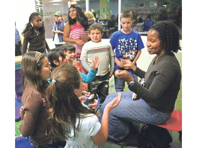 Northlake Hills fifth-grade teacher Jennetta Thomas gives rewards to Castaic Union School District students on Tuesday for correctly answering a question regarding a Thanksgiving book they read at the Castaic Public Library as part of the Grand Reader program. The program is an effort by the Castaic district and library hopes to get children and their families to read together outside of school.