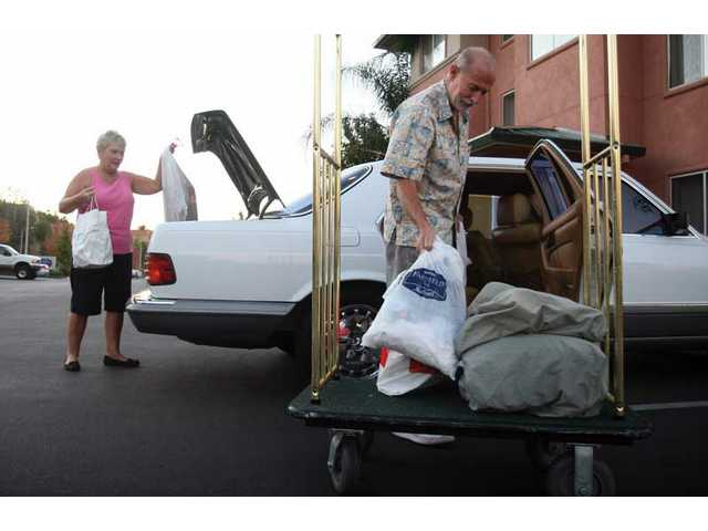 Judy and Ken Miller unpack the rest of their belongings from their car after having to evacuate from the Oakridge Mobile Home Park they called home for the last four years. The Millers are one of the few families whose homes are still standing.
