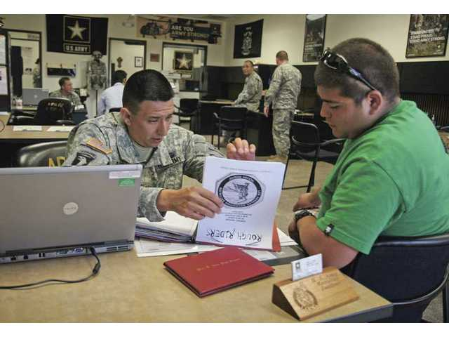U.S. Army Recruiter Staff Sergeant Jose Arellano, left, looks over the file of 19-year-old Heriberto Teran on Wednesday in Santa Clarita.