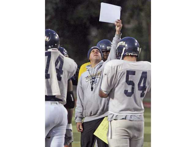 College of the Canyons defensive coordinator Bart Hansen, middle, shows the defense the play during practice on Wednesday at Cougar Stadium.