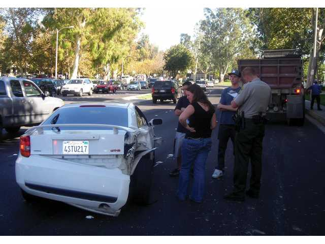 Nolan Divine, second from right, gives his account of a Wednesday morning traffic collision to Santa Clarita Valley Sheriff's Deputy Kirk Petersen. Noelle Saver and Fernando Ballasteros inspect the damage.