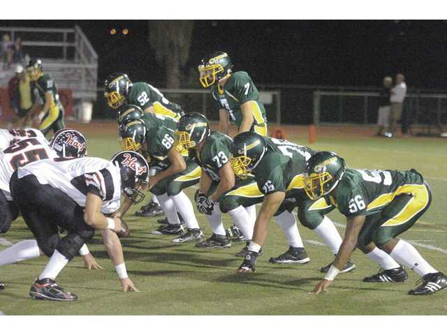 Canyon's offense, led by sophomore quarterback Jonathan Jerozal (7), lines up against Hart on Oct. 23. A flip of the coin put the Cowboys in the playoffs, but they will need more than luck to stay there. Canyon's first test will be tonight when the team travels to Moorpark High School for a 7:30 p.m. matchup.