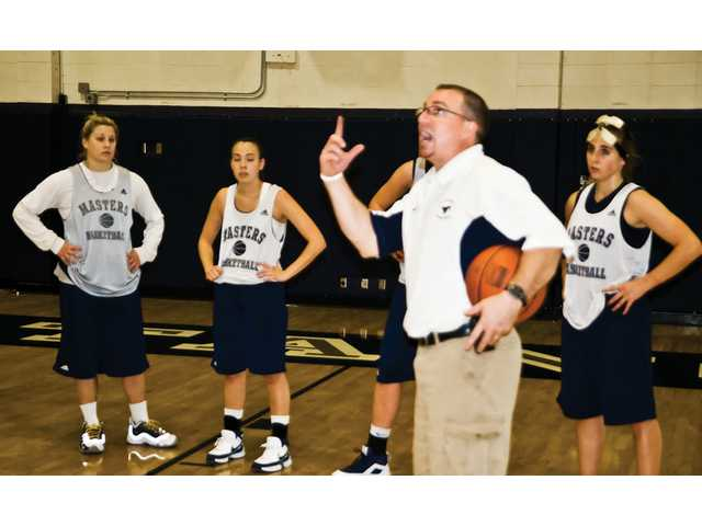 The Master's College head women's basketball coach Dan Waldeck, foreground, talks to his players during practice Wednesday.