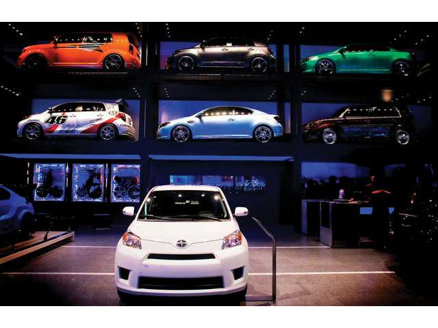 A wall of Toyota Scions in the West Hall of the Los Angeles Auto Show looms over more Scions on the floor.