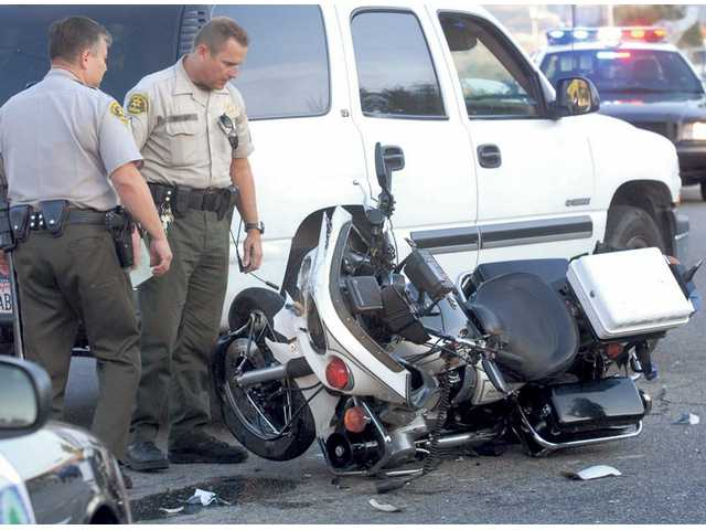Sheriff's deputies gather evidence at the scene where a sheriff's officer was injured in a crash involving his motorcycle and a pickup truck at Newhall Avenue and Railroad Avenue, near Hart Park in Newhall on Friday. The officer's injuries were apparently minor.