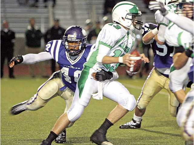 Valencia's Darrol Mitchell (48) sacks Thousand Oaks quarterback Jackson Lucht (13) Friday night at Valencia High School.
