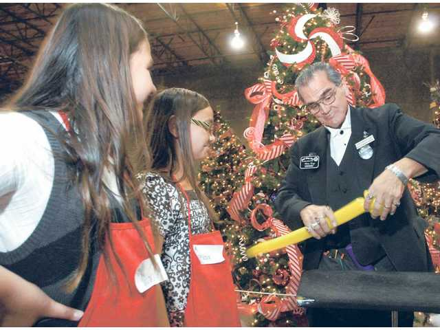Rev. Christopher Cory, Ph.D. makes a bird from a yellow balloon for 11-year-old twins Victoria and Melissa Simon at the seventh annual Festival of Trees on Centre Point Parkway in Santa Clarita on Friday. The festival was a three-day event to benefit the Boys & Girls Club of the Santa Clarita Valley.