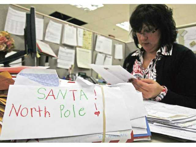 United States Postal Service Acting Manager Alicia Delgadillo reads over 'Dear Santa' letters at the Castaic post office on Friday. The Los Angeles Postal Service has ended Operation Santa after a registered sex offender tried to answer some of the letters.