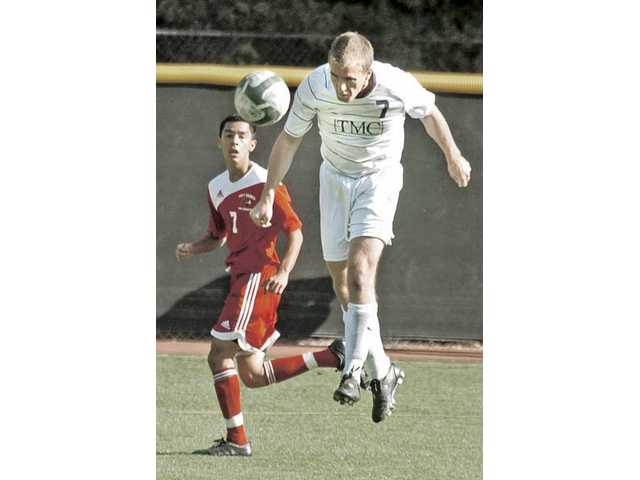 The Master's College defender Tyler Salvey (7) heads the ball on goal as Jesus Hernandez (7) of Holy Names looks on during the opening round of the NAIA Tournament on Saturday at Reese Field. The Mustangs won 1-0 and advanced to play Indian Tech on Monday in Fresno.