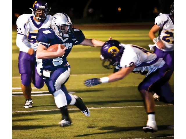 Saugus High's Ryan Zirbel (5)  breaks a tackle by Righetti High of Santa Maria's Lano Valera (45) in the Centurions' win on Friday night at Cougar Stadium.