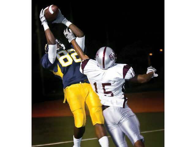 College of the Canyons' Teveon Burke (82) catches a touchdown over Antelope Valley's Tramell Joinerin (15) the third quarter of the Cougars' 41-17 win on Saturday.