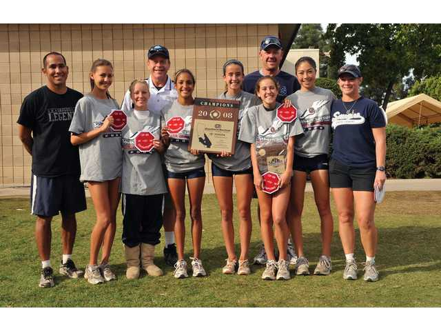 Members of the Saugus girls cross country team, including head coach Rene Paragas, left, show off their CIF-SS Division II Cross Country Championship plaque Saturday at Mt. SAC in Walnut.