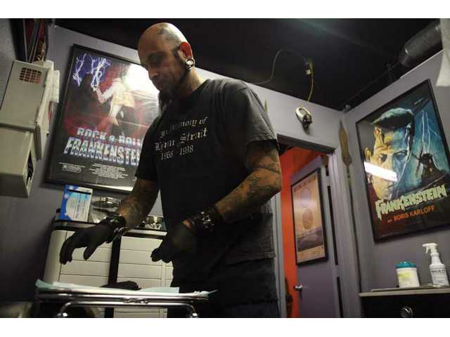 Rob Arvizu, who has been working on and off at the Just Passing Thru body-piercing studio in Newhall, starts his afternoon by preparing the proper tools he'll need to perform piercings later that day.