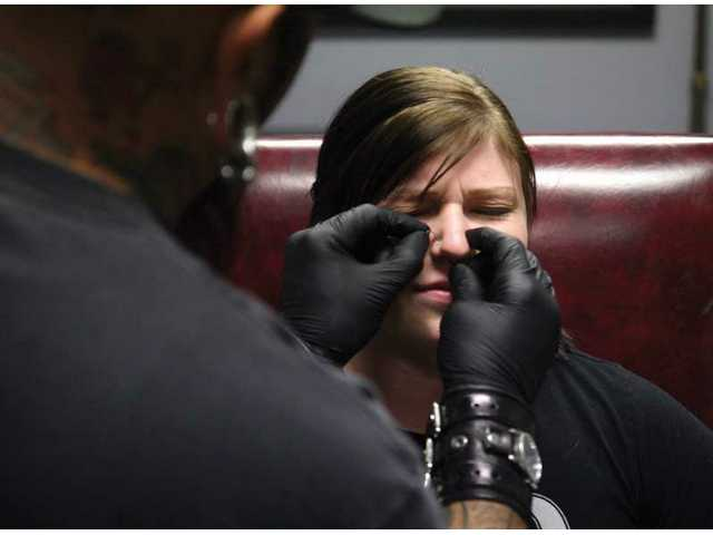 Allison Retig, 19, from Saugus, gets her nose pierced by Rob Arvizu at the Just Passing Thru body piercing shop in Newhall Friday afternoon.