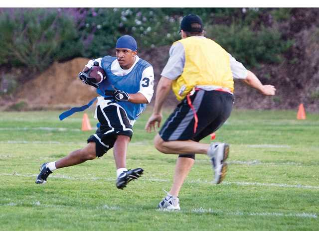 Jon Bird runs past Rob Muir during the Special Needs And Peers flag football's last season practice. This is the second year that LETMESAIL has teamed up with College of the Canyons.