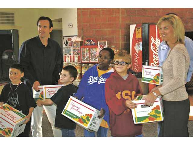 Assemblyman Cameron Smyth, back left, helps deliver 25 turkeys Tuesday with Valencia Water Company staff Josh Eppenbaugh and Beverly Johnson, right, to the SCV Boys & Girls Club in Newhall.