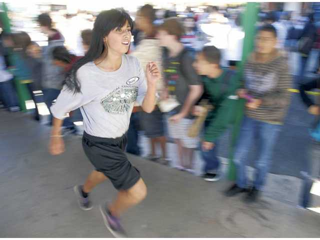 Dianna Gonzalez is cheered on by her schoolmates as she finishes in 11th place for the 7th-grade girls during the Turkey Trot food drive at Sierra Vista Junior High School in Canyon Country on Tuesday.