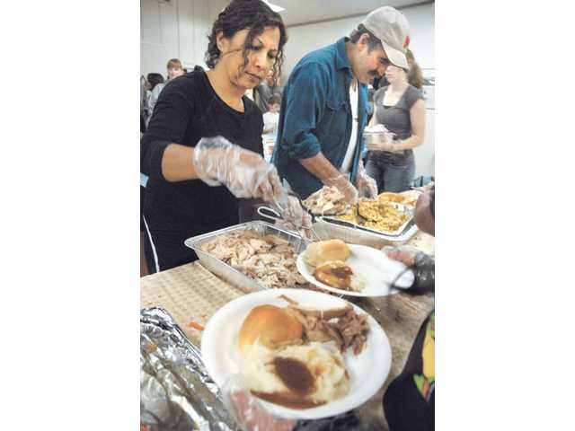 Bertha O'Donnell, left, and Gary Hilton joined volunteers who helped serve an estimated 525 turkey dinners provided by Real Life Church of Valencia to all who attended a Thanksgiving feast at the Val Verde Community Center on Tuesday night.