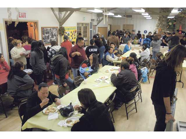 The multi-denominational Real Life Church of Valencia brought 93 volunteers to help provide the holiday feast to families in Val Verde Tuesday night.