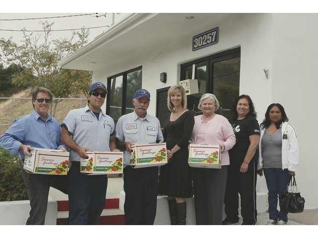 Left to right: Ed Masterson, field representative for Assemblyman Cameron Smyth; Chris Saenz, Jerold Graves and Beverly Johnson of Valencia Water Company; Jackie Bick, field representative for Senator George Runner; Beverly Ramirez, SDFHC volunteer, and Balvina Ortiz, one of the SDFHC patients who received a turkey.