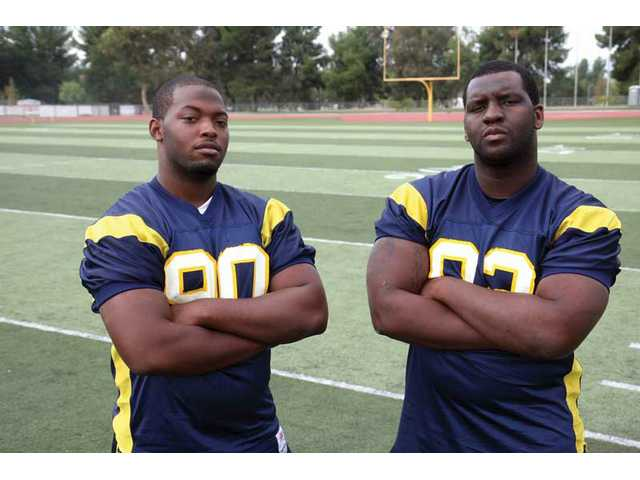 (Left and right) College of the Canyons football players Dejuan Yates and Jonathon Hollins both play nose guard for the Cougars and have garnered the attention of major universities.