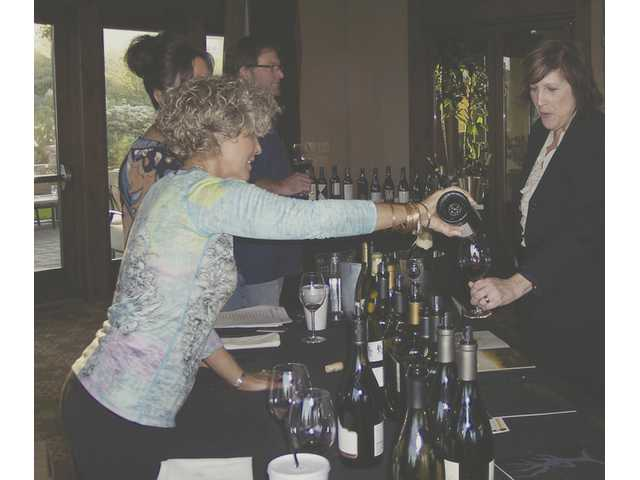 Guests gather around for a taste of one of the more than 150 wines available to sample at the fourth annual Valencia Wine Company Holiday Wine Tasting held Sunday at the Tournament Players Club in Valencia.