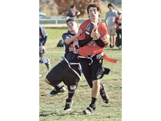 Andrew Fanfarssian, left, of the Blue team reaches for the flags of Joseph Simili of the Red team as he catches a touchdown pass in the seventh annual Rio Norte Junior High School Turkey Bowl football game.